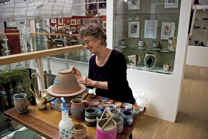 A woman painting ceramic pots